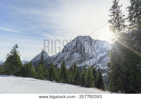 Winter Scenery With The Sun Shining Over The Snowy Austrian Alps, The Green Forest And White Valley,
