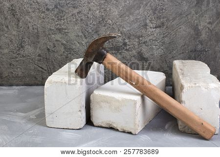 Silicate Bricks, Hammer On The Gray Concrete Background. Copy Space. Top View.