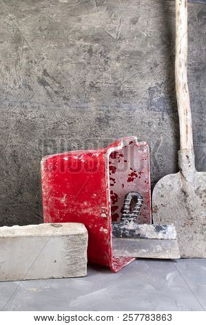 Building Tools Old, Dirty Shovel , Red Bucket, Bricks On The Gray Concrete Background. Copy Space. T