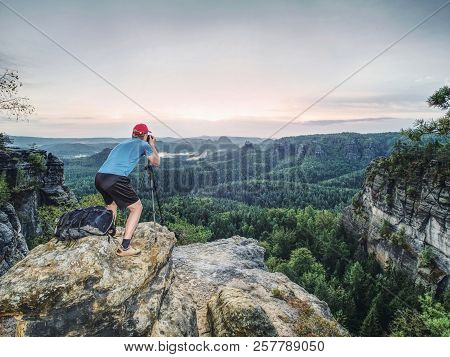 Photographer Or Videographer  Traveler With Heavy Backpack And Tripod In Hand Is Preparing For Art W