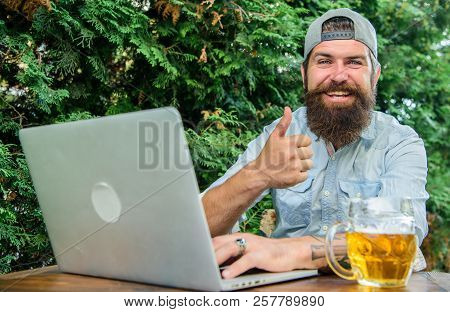 Football Fan Bearded Hipster Make Bet Sport Game Laptop. Guy Sit Terrace Outdoors With Beer. Betting