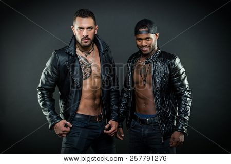 Machos with muscular torsos look attractive in leather jackets, dark background. Masculinity and brutality concept. Men with sexy muscular torsos look brutally. Men on confident faces with bristle. poster