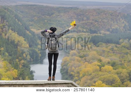 Girl With A Backpack And A Hat Standing On A Hill. Hands Raised Up. River And Mountains Below. Back