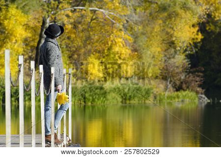 Girl In A Hat With Leaves In Hands Standing On The Dock. Autumn, Sunny. Side View