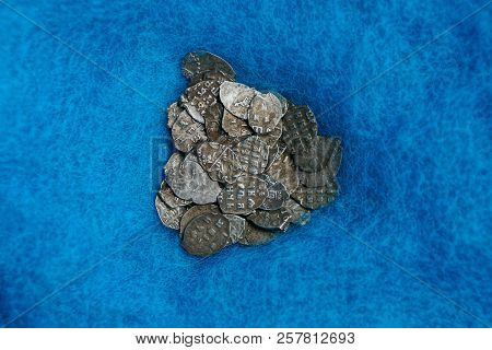 A Pile Of Old Coins Of Silver Scales On Blue Woolen Cloth