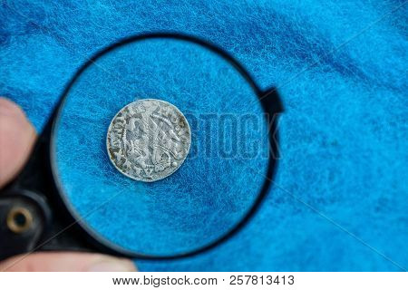 Old Silver Coin Under Magnifying Glass On Blue Cloth