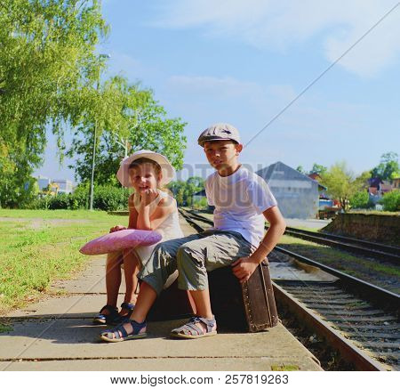 Adorable Little Girl And Boy On A Railway Station, Waiting For The Train With Vintage Suitcases. Tra