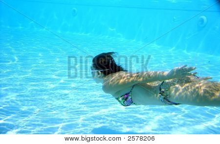 Woman Diving In Swimming Pool With Reflections