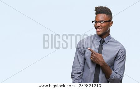 Young african american business man over isolated background cheerful with a smile of face pointing with hand and finger up to the side with happy and natural expression on face looking at the camera.