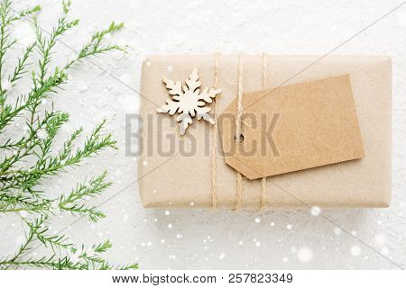 Christmas Gift Wrapped In Kraft Paper With Empty Tag. Glowing Snow Bokeh, Coniferous Branch On White