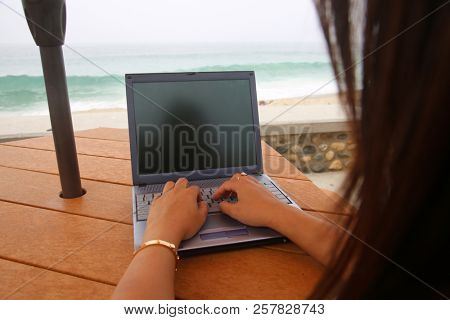 woman on laptop outdoors. room for text. online shopping. wireless internet. Woman on laptop at the beach.