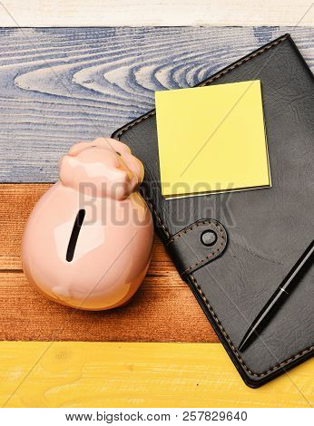 Moneybox With Pig Face Near Organizer And Pen.