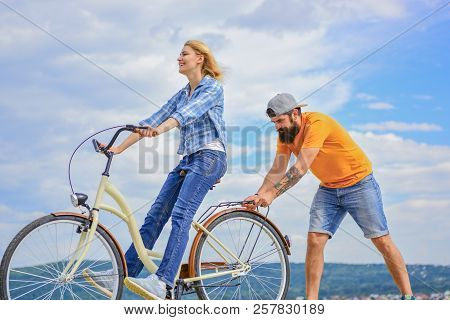Woman Rides Bicycle Sky Background. How To Learn To Ride Bike As An Adult. Girl Cycling While Boyfri