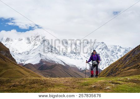 Tourist with a backpack in a hike. Trekking near the mountain Shkhara. Main Caucasian ridge. Zemo Svaneti, Georgia. Autumn landscape with a peak in the snow