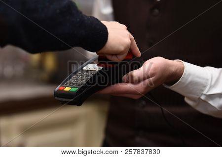 Cashier Holds Credit Card Reader On Defocused Background