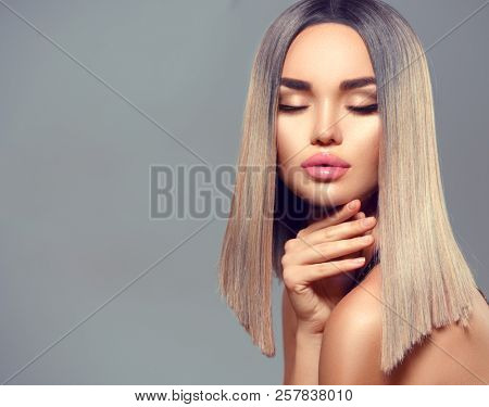 Trendy fashion hairstyle, haircut, ombre dyed hair. Beauty Model girl with perfect healthy hair and beautiful makeup posing in studio, young woman portrait on grey background