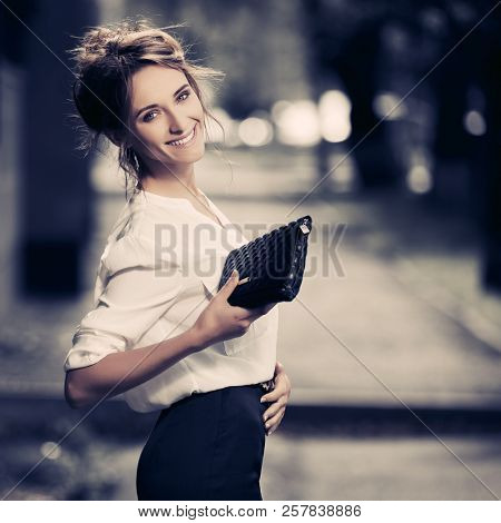 Happy young business woman with handbag walking in city street Stylish fashion model with bun updo hair wearing white shirt and pencil skirt