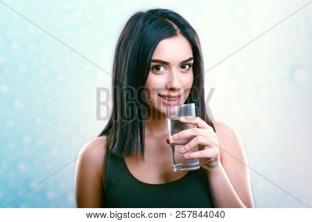 Young smiling woman holding and drinking water glass. Hydration concept