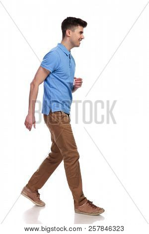 side view of a young casual man walking on white background