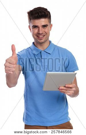 happy casual man working on tablet makes ok sign on white background