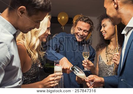 Young man pouring champagne in glasses for new year eve party. Happy and smiling girls and guys celebrating with sparkling white wine. Cheerful group of friends enjoying house party.