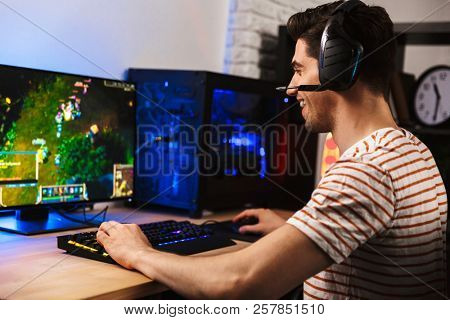 Portrait of professional gamer guy playing video games on computer wearing headphones and using backlit colorful keyboard