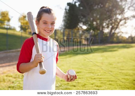 Young girl holding baseball and baseball bat looks to camera