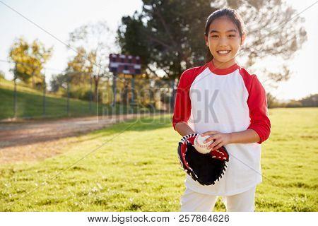 Chinese schoolgirl holding baseball and mitt smiling