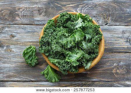 Fresh Green Curly Kale Leaves On A Wooden Table. Selective Focus. Rustic Style. Healthy Vegetarian F