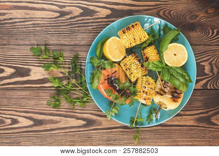 Corn Baked In Olive Oil, With Pepper, Salt And Basil On Blue Dish On A Light Surface. Vegetarian, Ve