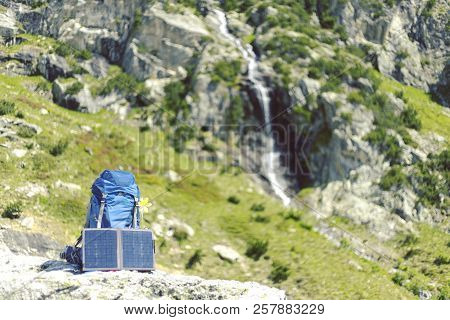 The Backpack Stands On A Trail In The Background Of The Mountains. The Sun Panel Hangs On The Backpa