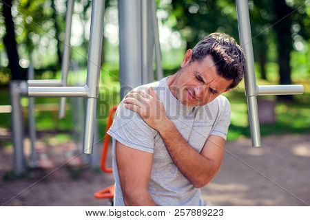 A Man Feeling Pain In His Shoulder During Sport And Workout In The Park. Sport, Medicine And People