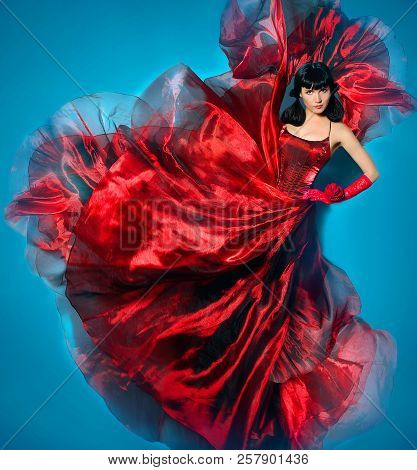 A Girl In A Bright Red Dress Is Dancing. Young Beauty Woman In Red Waving Flying Dress. Dancer In Si