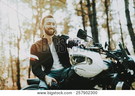 Motorcycle Biker Stops On Highway In A Forest. Speed Vehicle. Cool Rider With A Leather Jacket. Moto