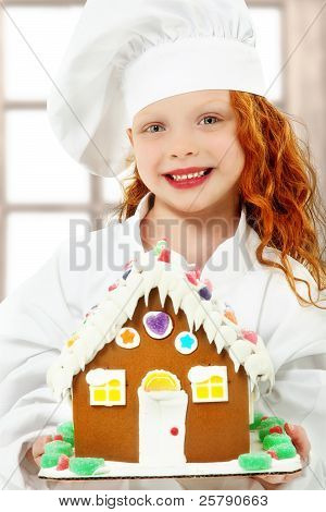 Girl Child In Chef Uniform Holding Ginger Bread Gingerbread House