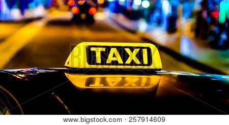 Night Picture Of A Taxi Car. Taxi Sign On The Car Roof Glowing In The Dark