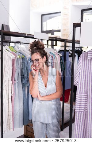 Jovial Female Showroom Owner Chatting On Phone