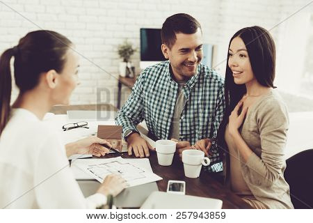 Young Man And Woman With Smiling Realtor In Office. Blueprint On Wooden Desk. Real Estate Concepts.