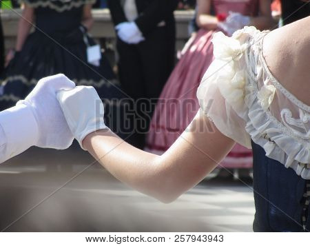 Close Up Of Couple Hands In White Gloves During Historical Dance . Loveliness And Prettiness Couple