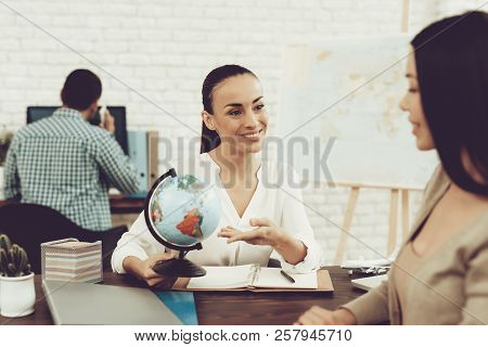 Young Woman In Travel Agency With Smiling Manager. Consultant In Travel Agency. Travel And Journey C