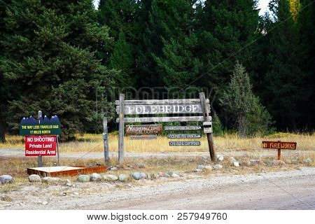 """POLEBRIDGE, MONTANA, USA - September 9, 2018: Welcome to Polebridge sign with business advertising and """"No Fireworks"""" signs"""