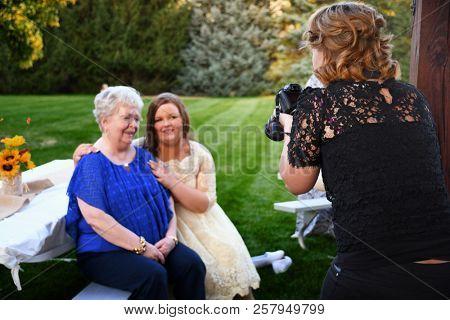 COEUR d'ALENE, IDAHO, USA - September 1, 2018: A wedding photographer prepares her camera during a photo shoot with a bride and her grandmother