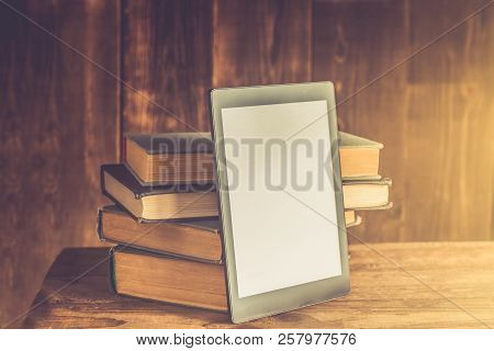 Ebook, Digital Tablet Device, With Old Real Books Nearby On The Rustic Background