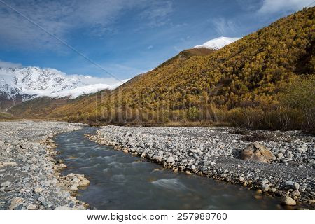 Autumn landscape with a mountain river Enguri. View to the top of Shkhara. Main Caucasian ridge. Zemo Svaneti, Georgia