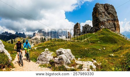 Tourist cycling in Cortina d'Ampezzo, stunning Cinque Torri and Tofana in background. Woman and man riding MTB trail. South Tyrol province of Italy, Dolomites. poster