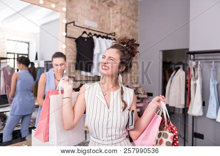 Jovial Female Client Completing Shopping In Showroom