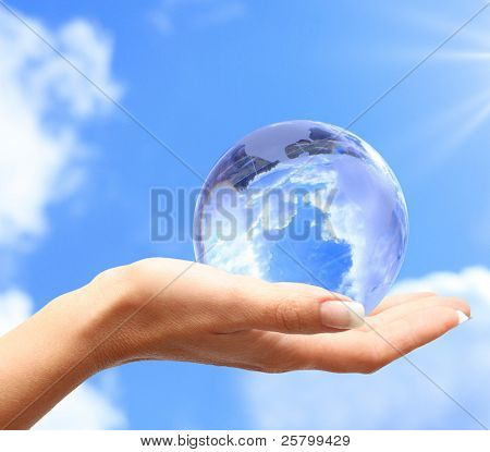 Globe in human hand against blue sky. Environmental protection concept.