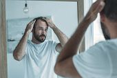 cropped shot of middle aged man with alopecia looking at mirror, hair loss concept poster