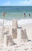 Young kids having fun in gorgeous ocean by sand castles poster