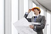 Architector in hardhat and business suit with construction plans poster